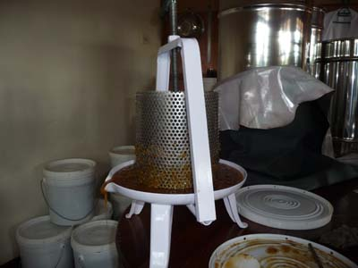 A simple hand wounded honey press filled with honey combs