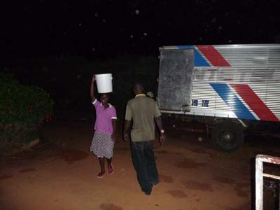 House girl helping out in the offloading. Ugandans have very strong necks.